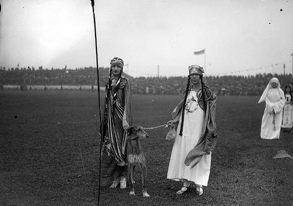 Two women in ancient Irish dress at the 1928 Tailteann Games. Note the lone nun in the background. This photo points to the divide and lack of options that Irish women faced in the decades after Irish Independence was declared.