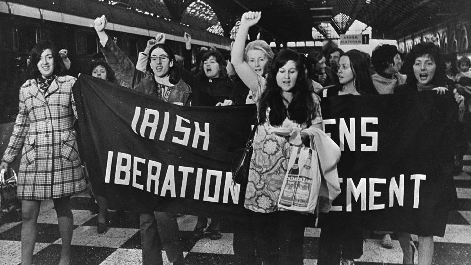 FOR THE ATTENTION OF JENNY RICKETT - CONTRACEPTIVE TRAIN Women on the platfrom of Connolly Station, Dublin in 1971 prior to bording the Belfast Train to buy contraceptives, which were illegal in the Republic in the 1970s and 1980s. (Nell McCafferty if pictured second left, chin partially obscured by the banner. Pic: The Irish Times SOURCE-Copy Neg
